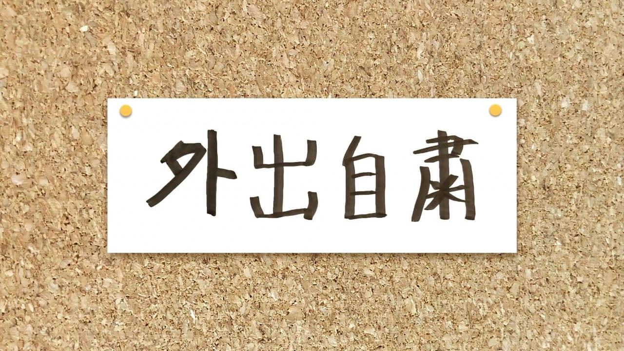 コルクボードに貼られた「外出自粛」と書かれた紙