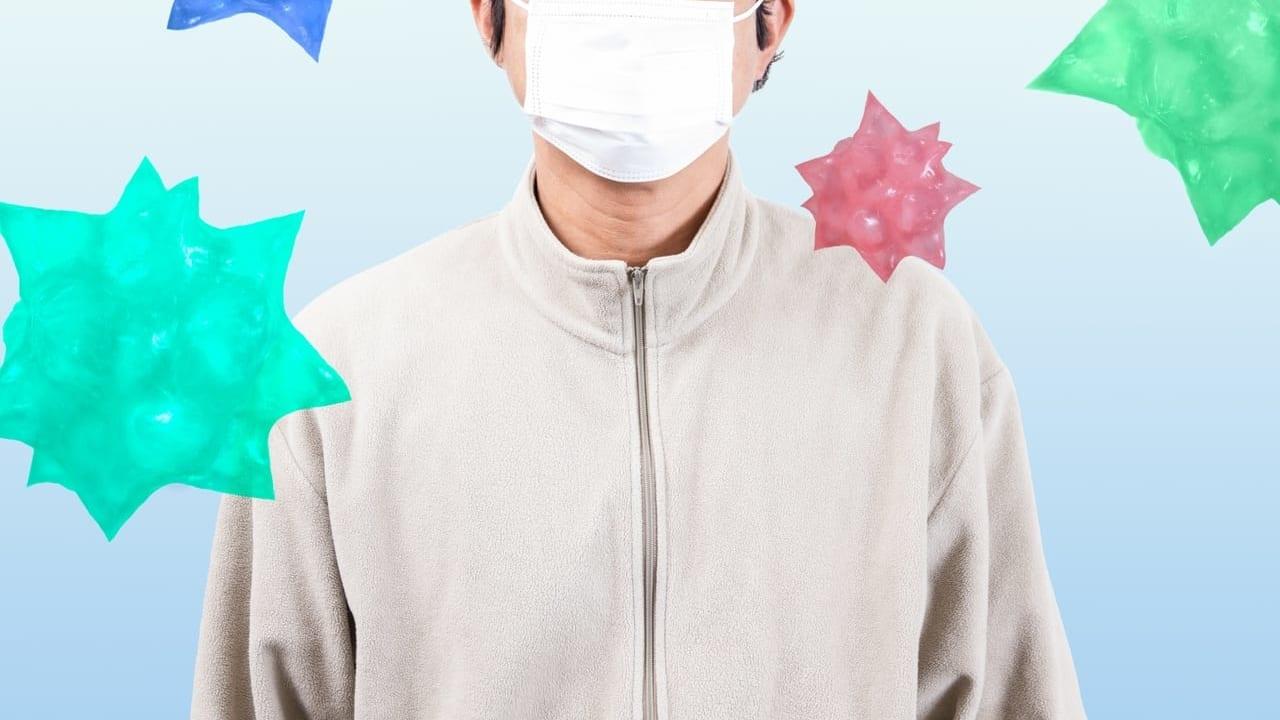 マスク姿の中年男性と空間に漂うウイルスのイメージ
